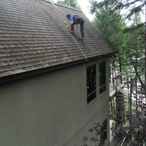 man working on tall house roof